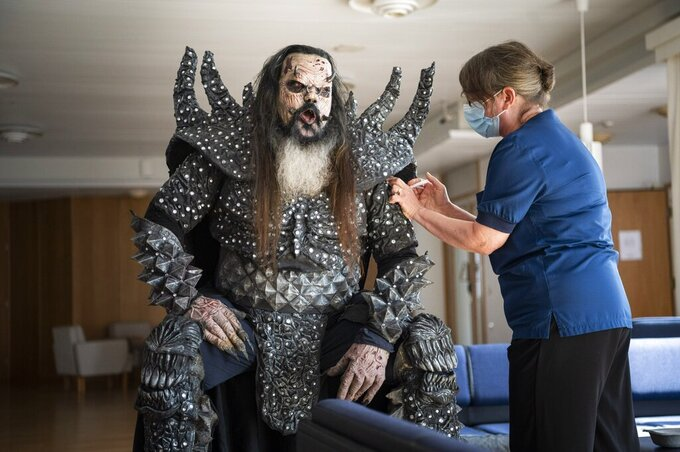 Mr Lordi of the Finnish hard rock band Lordi receives his second Covid-19 vaccination from nurse Paula Ylitalo in Rovaniemi, Finland, Sunday, Aug. 1, 2021. (Jouni Porsanger/Lehtikuva via AP)