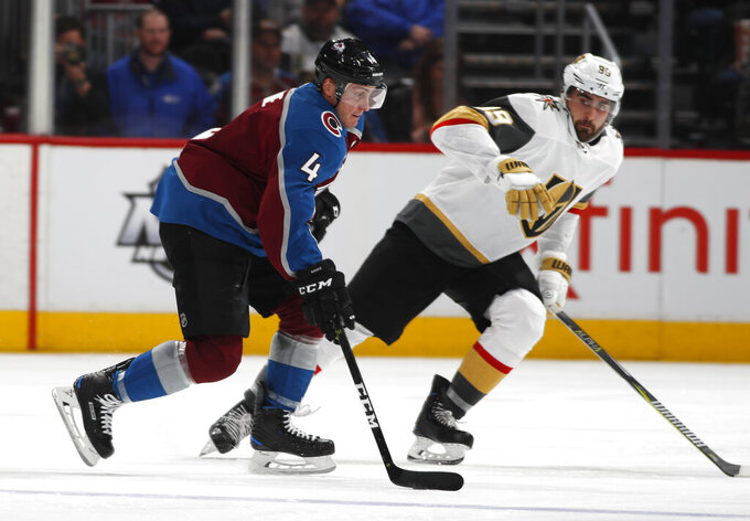 Colorado Avalanche defenseman Tyson Barrie, left, looks to shoot the puck past Vegas Golden Knights right wing Alex Tuch during the second period of an NHL hockey game Wednesday, March 27, 2019, in Denver. (AP Photo/David Zalubowski)