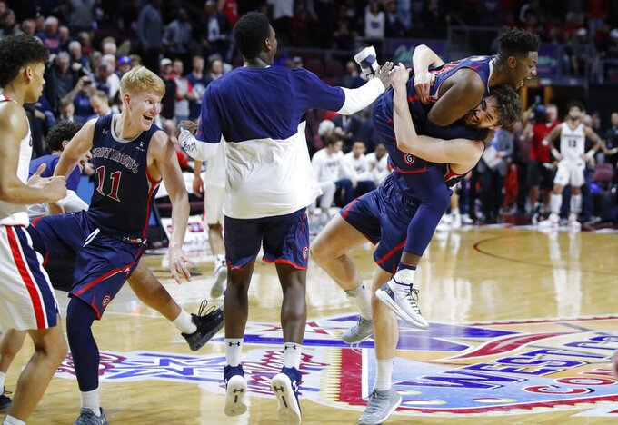 St. Mary's Jordan Hunter, right, and Malik Fitts, second from right, celebrate after their team defeated Gonzaga 60-47 in an NCAA college basketball game for the West Coast Conference men's tournament title, Tuesday, March 12, 2019, in Las Vegas. (AP Photo/John Locher)