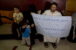 In this May 27, 2019, photo, Waseem, father of 5-year-old Aisha a-Lulu, holds the hospital bed sheet his deceased daughter was covered with when she was sent home from a Jerusalem hospital, at the family home in Burij refugee camp, central Gaza Strip. The death of the Palestinian girl has drawn attention to Israel's vastly complex system for issuing travel permits to Gaza medical patients and their families.  (AP Photo/Hatem Moussa)