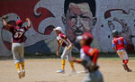 Youths play baseball at a field decorated with a mural of Venezuela's late President Hugo Chavez in Caracas, Venezuela, Tuesday, March 5, 2019. On Tuesday, which marks six years after his death from cancer, Chavez continues to unleash mixed feelings among Venezuelans: some remember him as the father of a revolution that defended the poor, while others blame him for the deep and prolonged crisis that overwhelms the South American country. (AP Photo/Eduardo Verdugo)