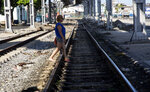 A woman crosses the railroad tracks in Havana, Cuba, Wednesday, May 22, 2019. Much of Cuba's remaining railroad equipment, much of it dating from 1975, lies in disrepair on the sides of rail yards as the system has seen the number of passengers plunge in recent decades. (AP Photo/Ismael Francisco)