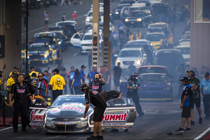 Pro Stock driver Jason Line's crew assists him in preparing for a qualifying round during the Dodge Mile-High NHRA Nationals auto race at Bandimere Speedway, Friday, July 19, 2019, in Morrison, Colo. A judge decided on Tuesday, July 21, 2020, against sanctioning the drag strip for violating social distancing rules during a July 4 event but ordered track owners to abide by public health directives to stem the spread of the new coronavirus. (Kelsey Brunner/The Denver Post via AP)