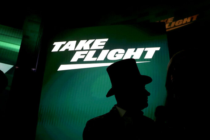 A fan wears a top hat waits for an event unveiling the New York Jets' new NFL football uniforms Thursday, April 4, 2019, in New York. (AP Photo/Julio Cortez)