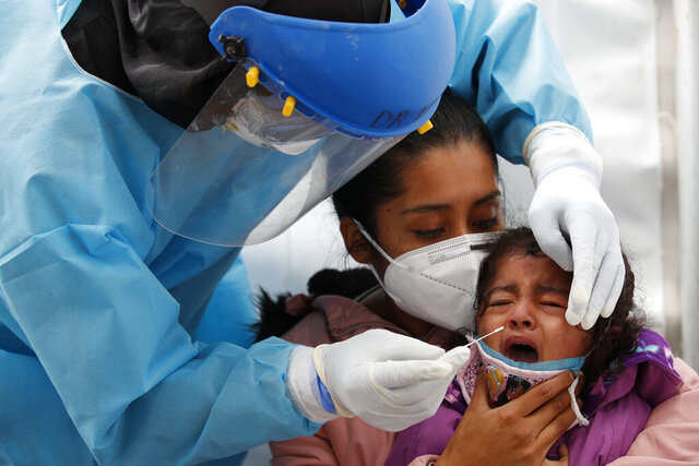 Dr. Victor Hugo Santamaria tests 2-year-old Regina Chavez for COVID-19 as she is held by her mother Edith Monserrat Bautista, in a tent set up to perform rapid coronavirus testing at the TAPO bus station in the Venustiano Carranza borough of Mexico City, Friday, Nov. 20, 2020. Mexico passed the 100,000 mark in confirmed COVID-19 deaths on Thursday, becoming only the fourth country to do so. (AP Photo/Rebecca Blackwell)
