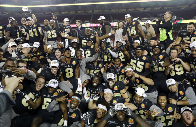 FILE - In this Dec. 27, 2017, file photo, Purdue players celebrate after a 38-35 win over Arizona during the Foster Farms Bowl NCAA college football game, in Santa Clara, Calif. The overall graduation rates for athletes on bowl-bound FBS football programs continues to climb, though the disparity in the rates between white and African-American players widened slightly, according to  a study released on Monday, Dec. 3, 2018.  (AP Photo/Marcio Jose Sanchez)