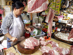In this Thursday, May 16, 2019, photo, vendor Khov Sokhouy, 56, cuts pork to sell to customers at the Phsar Kandal market in Phnom Penh, Cambodia. Pork lovers worldwide are wincing at prices that have jumped by up to 40 percent as China's struggle to stamp out African swine fever in its vast pig herds sends shockwaves through global meat markets. Potential shortages are a more serious concern in places such as Cambodia where pork is the only meat many families can afford. (AP Photo/Heng Sinith)