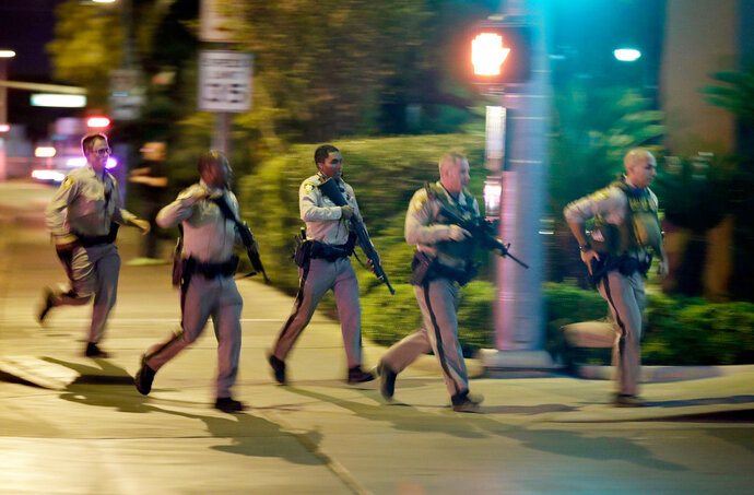 FILE - In this Oct. 1, 2017, file photo, police run toward the scene of a shooting near the Mandalay Bay resort and casino on the Las Vegas Strip in Las Vegas. In documents made public Thursday, Dec. 27, 2018, police in Las Vegas have released transcripts of some officers' accounts about what they saw, heard and did trying to locate and stop a gunman who unleashed the deadliest mass shooting in the nation's modern history almost 15 months earlier. (AP Photo/John Locher, File)