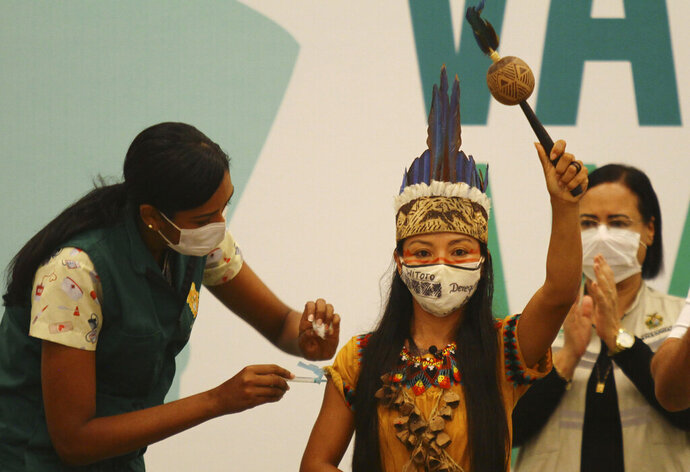 Health worker Vanda Ortega, from the Witoto Indigenous group and dressed in traditional clothing, is the first woman to receive the COVID-19 vaccine produced by China's Sinovac Biotech Ltd, during the start of the vaccination program in Manaus, Amazonas state, Brazil, Monday, Jan. 18, 2021. (AP Photo/Edmar Barros)