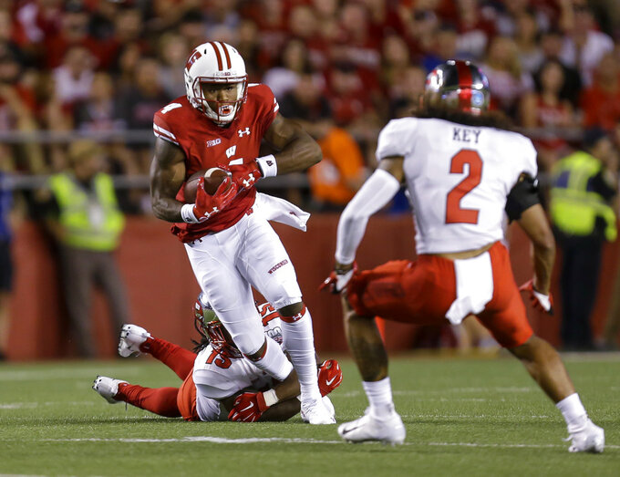FILE - In this Aug. 31, 2018 file photo, Wisconsin wide receiver A.J. Taylor, left, makes a reception between Western Kentucky's Ta'Corian Darden and Devon Key (2) during the first half of an NCAA college football game in Madison, Wis. Taylor is off to a fast start for the sixth-ranked Wisconsin Badgers as they get ready to play BYU this weekend. Taylor had a career-high 134 yards with a touchdown on five catches last week against New Mexico. He has carried the load at the wideout position at a time when the receiving corps was thinned out by suspensions to Quintez Cephus and Danny Davis.   (AP Photo/Andy Manis, File)