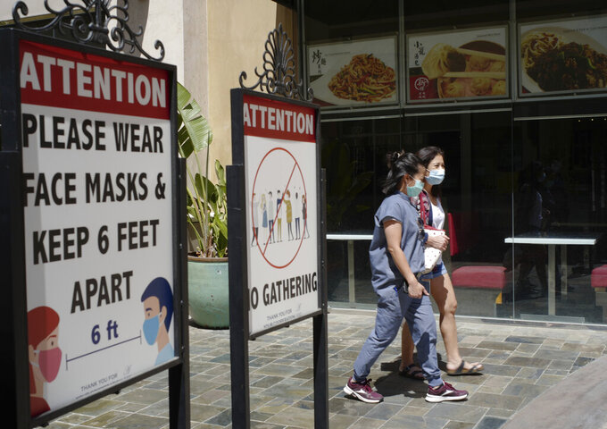 FILE - In this June 11, 2021, file photo, customers wear face masks in an outdoor mall with closed businesses amid the COVID-19 pandemic in Los Angeles. California regulators on Thursday, June 17, 2021, are set to approve revised worksite pandemic rules that allow fully vaccinated employees the same freedoms as when they are off the job. (AP Photo/Damian Dovarganes, File)