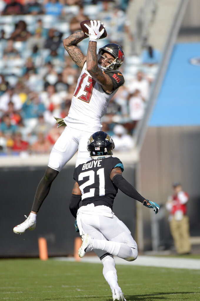 Tampa Bay Buccaneers wide receiver Mike Evans (13) catches a pass over Jacksonville Jaguars cornerback A.J. Bouye (21) during the second half of an NFL football game, Sunday, Dec. 1, 2019, in Jacksonville, Fla. (AP Photo/Phelan M. Ebenhack)