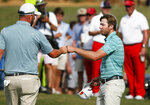 Marc Leishman, left, and Sam Burns, right, fist-bump on the 18th green following their second round of the AT&T Byron Nelson golf tournament in McKinney, Texas, Friday, May 14, 2021. (AP Photo/Ray Carlin)