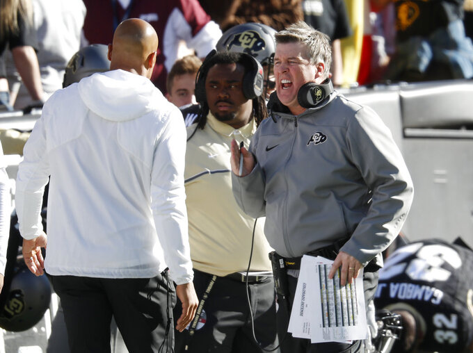 Colorado head coach Mike MacIntyre, right, confers with sideline personnel in the first half of an NCAA college football game against Washington State Saturday, Nov. 10, 2018, in Boulder, Colo. (AP Photo/David Zalubowski)