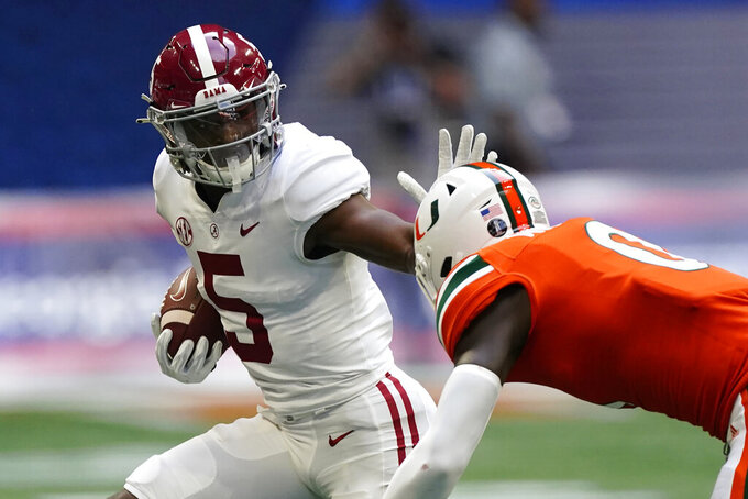 Alabama wide receiver Javon Baker (5) fends off Miami safety James Williams (0) as he runs after a catch during the second half of an NCAA college football game Saturday, Sept. 4, 2021, in Atlanta. (AP Photo/John Bazemore)