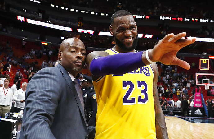 Los Angeles Lakers forward LeBron James waves to a fan after the team's NBA basketball game against Miami Heat on Sunday, Nov. 18, 2018, in Miami. (AP Photo/Brynn Anderson)