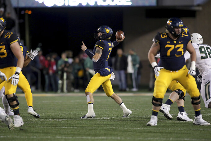 West Virginia quarterback Will Grier (7) attempts a pass during the first half of an NCAA college football game against Baylor, Thursday, Oct. 25, 2018, in Morgantown, W.Va. (AP Photo/Raymond Thompson)