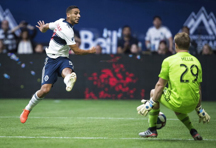 Vancouver Whitecaps' Ali Adnan, left, is stopped by Sporting Kansas City goalkeeper Tim Melia during the second half of an MLS soccer match Saturday, July 13, 2019, in Vancouver, British Columbia. (Darryl Dyck/The Canadian Press via AP)