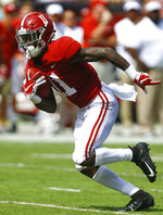 FILE - In this Sept. 29, 2018, file photo, Alabama wide receiver Henry Ruggs III (11) catches a pass and scores a touchdown during the first half of an NCAA college football game against Louisiana-Lafayette, in Tuscaloosa, Ala. No. 1 Alabama has one of the SEC's most talented collection of receivers, and the Crimson Tide is spreading it around among Jerry Jeudy, Henry Ruggs III, DeVonta Smith and Jaylen Waddle. (AP Photo/Butch Dill, File)