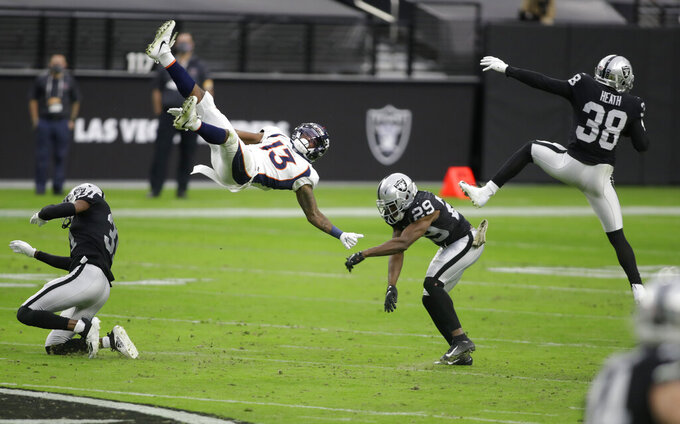 Las Vegas Raiders strong safety Jeff Heath (38) makes an interception on a pass intended for Denver Broncos wide receiver K.J. Hamler (13) who was covered by free safety Lamarcus Joyner (29) during the first half of an NFL football game, Sunday, Nov. 15, 2020, in Las Vegas. (AP Photo/Isaac Brekken)