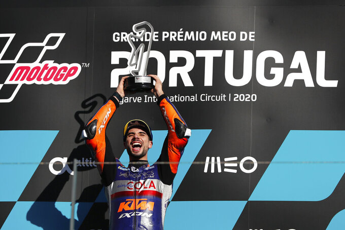 MotoGP rider Miguel Oliveira of Portugal celebrates on the podium after winning the MotoGP race of the Portuguese Motorcycle Grand Prix, the last race of the season, at the Algarve International circuit near Portimao, Portugal, Sunday, Nov. 22, 2020. (AP Photo/Armando Franca)