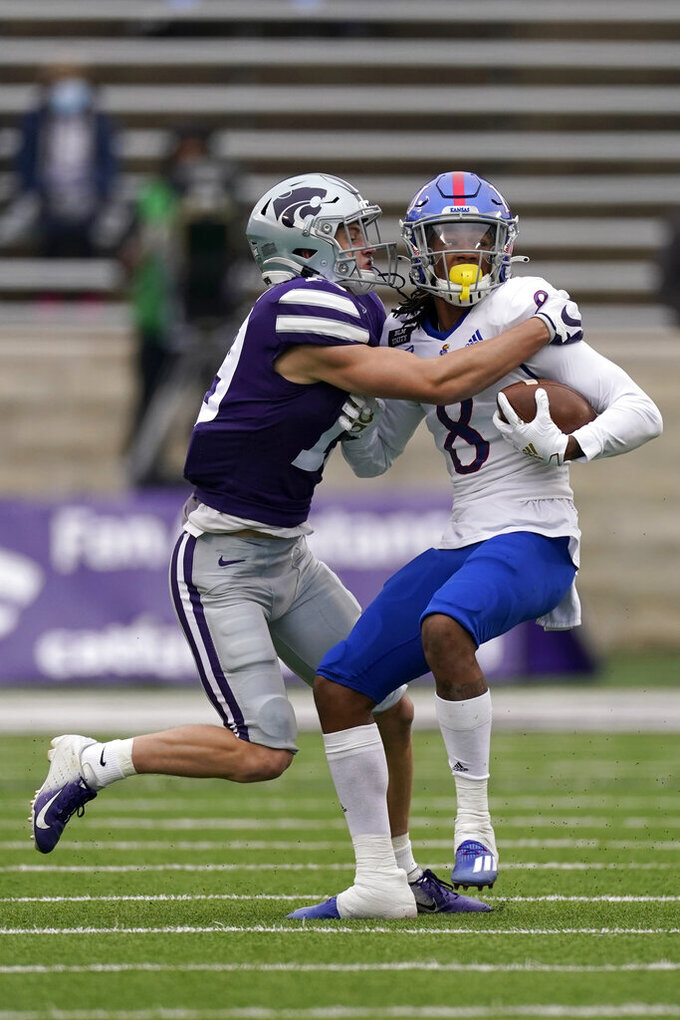 Kansas State defensive back Ross Elder (19) tackles Kansas wide receiver Kwamie Lassiter II (8) during the first half of an NCAA football game Saturday, Oct. 24, 2020, in Manhattan, Kan.. (AP Photo/Charlie Riedel)