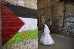 An ultra-Orthodox Jewish girl wearing costume walks next to a wall spray-painted with the Palestinian flag during celebrations of the Jewish holiday of Purim in the Mea Shearim neighborhood of Jerusalem, Sunday, Feb. 28, 2021. Purim commemorates the Jews' salvation from genocide in ancient Persia, as recounted in the biblical Book of Esther. (AP Photo/Oded Balilty)