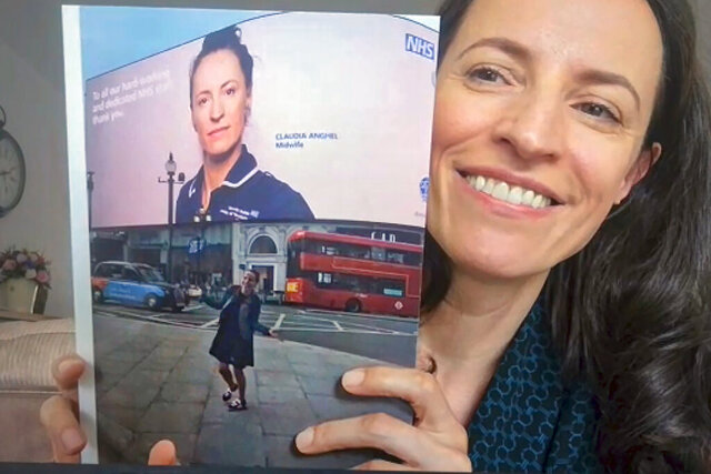 In this image taken from an online video interview with The Associated Press, Claudia Anghel, a Romanian midwife working in England, holds up a photograph of a large display in Piccadilly Circus showing her portrait shot by celebrity photographer Rankin, for a campaign celebrating the 72nd anniversary of the U.K.'s National Health Service, in Nuneaton, England, Tuesday, July, 28, 2020. Anghel's success story as one of 600,000 Romanians in Britain is at the same time a telling sign of how the deficiencies of her home country's health care system and the bleak prospects for a better future for herself and her family have left huge gaps in Romanian society and its health care system. (AP Photo)