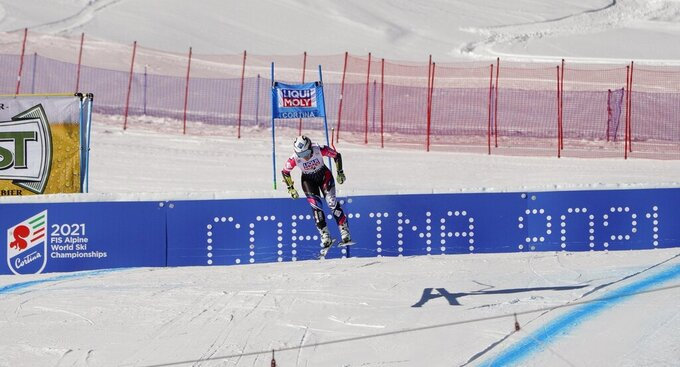 FILE - In this Jan. 20, 2019 file photo, Liechtenstein's Tina Weirather speeds down the course as a banner advertising the ski world championships in Cortina d'Ampezzo is seen in background, during an alpine ski, women's World Cup super-G in Cortina D'Ampezzo, Italy. The natural beauty of Cortina will be of special importance at the alpine ski World championships, with organizers hoping that the images from the slopes beamed around the globe to TV viewers will make up for the lack of fans amid the coronavirus pandemic. (AP Photo/Giovanni Auletta, File)