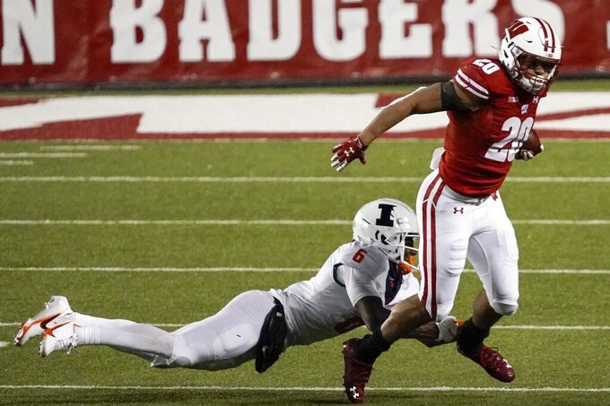 Wisconsin running back Isaac Guerendo tries to get away from Illinois defensive back Tony Adams during the second half of an NCAA college football game Friday, Oct. 23, 2020, in Madison, Wis. Wisconsin won 45-7. (AP Photo/Morry Gash)