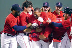 Boston Red Sox's Rafael Devers, center, is surrounded by teammates while celebrating his winning RBI-single in the bottom of the ninth inning of a baseball game against the Toronto Blue Jays at Fenway Park, Monday, June 14, 2021, in Boston. (AP Photo/Charles Krupa)