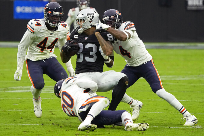 Chicago Bears free safety Eddie Jackson (4) and cornerback Duke Shelley (20) tackle Las Vegas Raiders tight end Darren Waller (83) during the second half of an NFL football game, Sunday, Oct. 10, 2021, in Las Vegas. (AP Photo/Rick Scuteri)