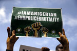 People hold banners as they demonstrate on the street to protest against police brutality in Lagos, Nigeria, Thursday Oct. 15, 2020. Protests against Nigeria's police continued to rock the country for the eighth straight day Thursday as demonstrators marched through the streets of major cities, blocking traffic and disrupting business. (AP Photo/Sunday Alamba)
