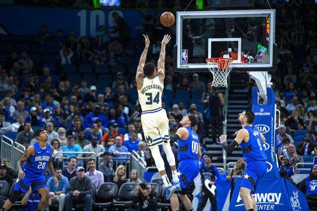 Milwaukee Bucks forward Giannis Antetokounmpo (34) shoots over Orlando Magic forward Aaron Gordon (00) during the first half of an NBA basketball game in, Orlando, Fla., Saturday, Feb. 8, 2020. (AP Photo/Willie J. Allen Jr.)