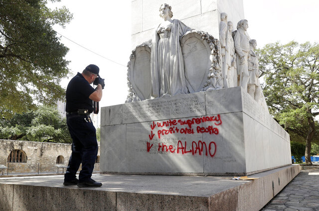 San Antonio Police Department Senior Crime Scene Investigator Robert Rackley collects evidence at the site where the Alamo Cenotaph was vandalised with spray paint in San Antonio, Friday, May 29, 2020. (AP Photo/Eric Gay)