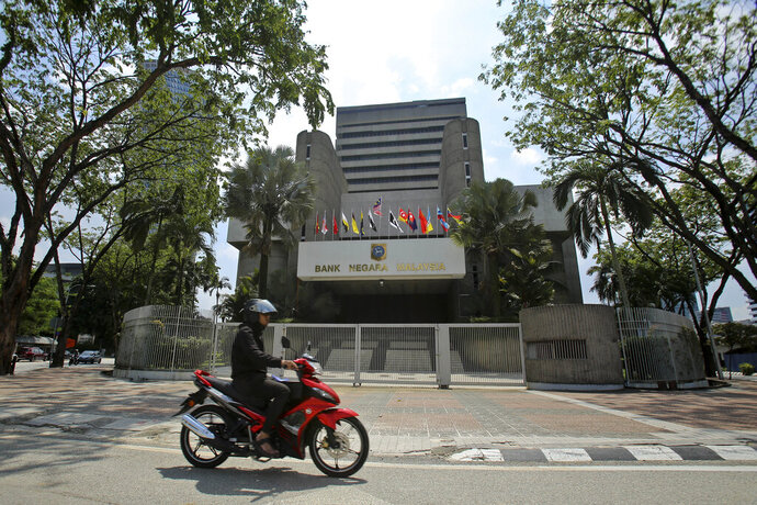 FILE - In this  June 6, 2018, file photo, a motorcyclist rides past the Bank Negara Malaysia in Kuala Lumpur, Malaysia. The country's central bank on Tuesday, May 7, 2019, cut interest rates for the first time in nearly three years to help support growth and counter risks from a global slowdown, trade tensions and extended weakness in commodity prices. (AP Photo/Sadiq Asyraf, File)