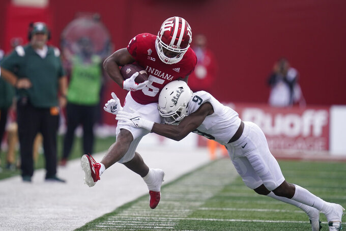 Indiana's Stephen Carr (5) is hit by Michigan State's Donald Williams during the second half of an NCAA college football game, Saturday, Oct. 16, 2021, in Bloomington, Ind. Michigan State won 20-15. (AP Photo/Darron Cummings)