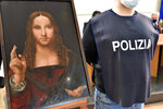 "An Italian police officer stands by a copy of the ""Salvator Mundi"" (Savior of the World) by Leonardo da Vinci, in Naples, Italy, Wednesday, Jan. 20, 2021. Italian police have recovered a copy of Leonardo da Vinci's 16th century ""Salvator Mundi"" painting of Jesus Christ that was stolen from a Naples church without the priests even realizing it was gone. The discovery was made over the weekend when Naples police working on a bigger operation found the painting hidden in an apartment. Police chief Alfredo Fabbrocini said the owner offered a ""less than credible"" explanation that he had ""casually"" bought it at a small market. (Italian Police via AP)"