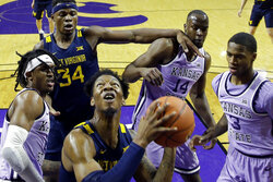 West Virginia's Gabe Osabuohien, center, looks to shoot between Kansas State's Cartier Diarra, left, and DaJuan Gordon (3) during the first half of an NCAA college basketball game Saturday, Jan. 18, 2020, in Lawrence, Kan. (AP Photo/Charlie Riedel)