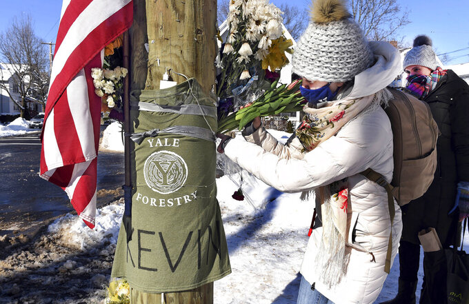 FILE — In this Feb. 8, 2021 file photo, Yale postdoctoral students Maria Kochugaeva, left, and Elvira Mulyukova leave flowers at a memorial for Yale School of the Environment grad student Kevin Jiang, near where he was killed. A fugitive wanted in the killing of Jiang in Connecticut in February was arrested Friday, May 14, 2021, in Alabama, U.S. marshals said. (Arnold Gold/Hearst Connecticut Media via AP, File)