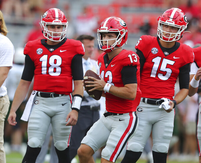 CORRECTS DATELINE TO ATHENS, GA., INSTEAD OF ATLANTA - Georgia quarterbacks JT Daniels, from left, Stetson Bennett and Carson Beck prepare to play UAB in an NCAA college football game on Saturday, Sept 11, 2021, in Athens, Ga. (Curtis Compton/Atlanta Journal-Constitution via AP)