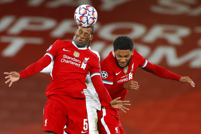 Liverpool's Georginio Wijnaldum heads the ball as he jumps with teammate Liverpool's Joe Gomez during the Champions League Group D soccer match between Liverpool and FC Midtjylland at Anfield stadium, in Liverpool, England, Tuesday, Oct. 27, 2020. (Phil Noble/Pool via AP)