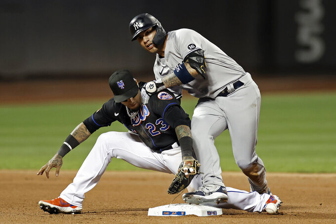 New York Yankees' Gleyber Torres, top, falls over New York Mets second baseman Javier Baez (23) after hitting a double during the seventh inning of a baseball game on Friday, Sept. 10, 2021, in New York. (AP Photo/Adam Hunger)