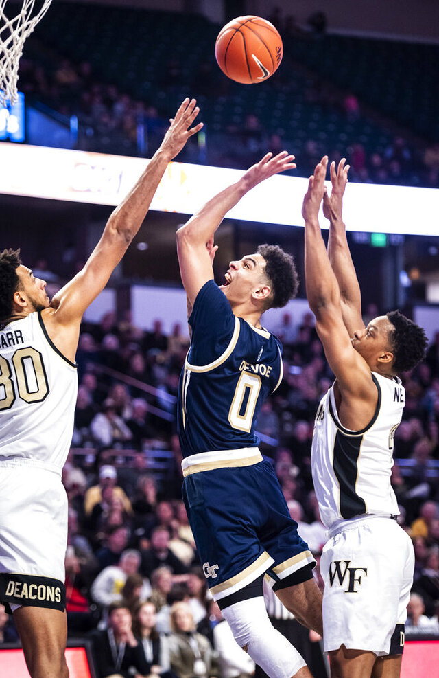 Georgia Tech guard Michael Devoe (0) shoots over Wake Forest center Olivier Sarr (30) during an NCAA college basketball game Wednesday, Feb. 19, 2020, in Winston-Salem, N.C. (Andrew Dye/The Winston-Salem Journal via AP)