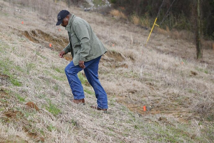 Supervisor Marvell Howard inspects the slope failure as he climbs up the side of the Oktibbeha County Lake dam west of Starkville, Miss., Wednesday, Jan. 15, 2020. Officials said a breach would affect an estimated 130 properties and nine highways. (AP Photo/Rogelio V. Solis)