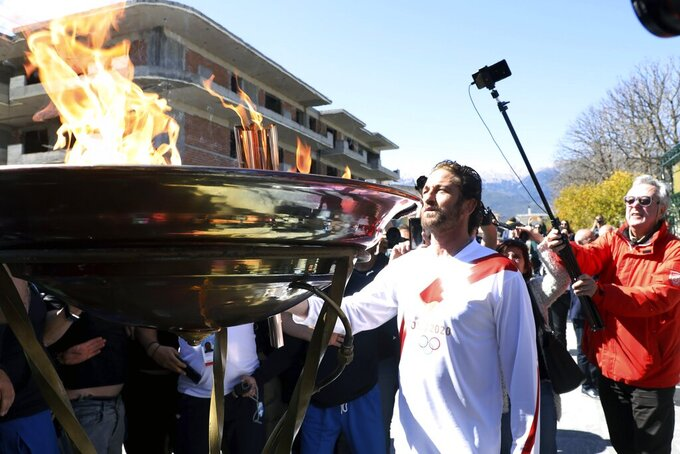 "US actor Gerard Butler lights an altar as a torchbearer during the Olympic torch relay of the 2020 Tokyo Olympic Games in the southern Greek town of Sparta, Friday, March 13, 2020. Greece's Olympic committee says it is suspending the rest of its torch relay for the Olympic flame due to the ""unexpectedly large crowd"" that gathered to watch despite repeated requests for the public to stay away to prevent the spread of the new coronavirus. (AP Photo)"