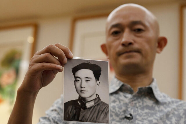 Zhang Hai holds up a photo of his father taken in his youth during an interview in Shenzhen in southern China's Guangdong province on Friday, Oct. 16, 2020. Zhang is demanding to meet a visiting World Health Organization expert team, saying it should speak with affected families who allege they are being muffled by the Chinese government.(AP Photo/Ng Han Guan)