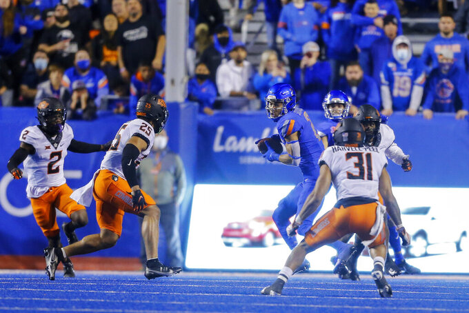 Boise State wide receiver Khalil Shakir (2) turns after a reception in front of Oklahoma State safety Jason Taylor II (25) and safety Kolby Harvell-Peel (31) during the second half of an NCAA college football game Saturday, Sept. 18, 2021, in Boise, Idaho. (AP Photo/Steve Conner)