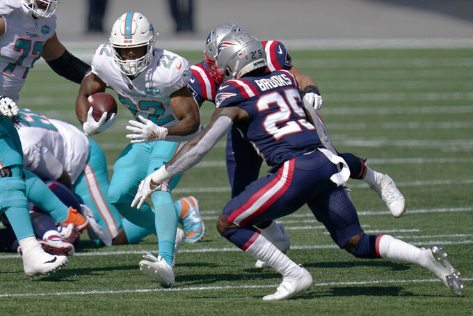 Miami Dolphins running back Matt Breida (22) carries the ball as New England Patriots defensive back Terrence Brooks (25) chases in the first half of an NFL football game, Sunday, Sept. 13, 2020, in Foxborough, Mass. (AP Photo/Charles Krupa)