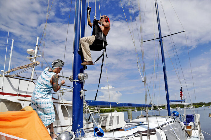 Lisa Vance helps her husband Stephan go up the mast of their sailboat to do a repair in preparation for Hurricane Dorian, Friday, Aug. 30, 2019, at the Vero Beach City Marina in Vero Beach, Fla. The National Hurricane Center says Dorian could hit the Florida coast as a major hurricane early next week. (AP Photo/Lynne Sladky)